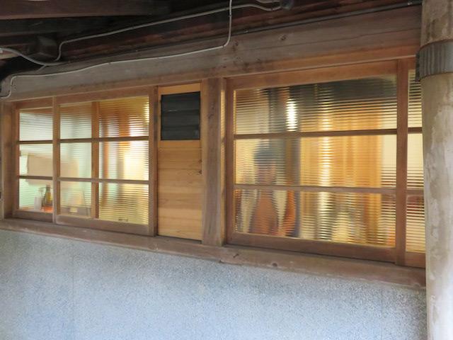 古い窓のスリガラス越しに台所で仕事される、なみさんの姿が見える
